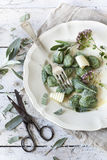 Homemade spinach dumplings with sage leafs, butter curls, flowers on plate on rustic background Royalty Free Stock Image