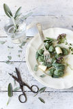 Homemade spinach dumplings with sage leafs, butter curls, flowers on plate on rustic background Stock Images