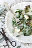 Homemade spinach dumplings with sage leafs, butter curls, flowers on plate on rustic background Royalty Free Stock Images