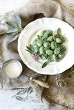 Homemade spinach dumplings with sage leafs and flowers on plate on rustic background Stock Images