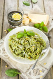 Homemade spinach pasta with pesto and Parmesan cheese Stock Photo