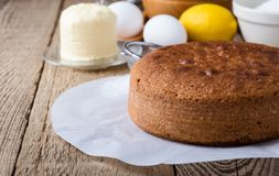 Homemade sponge cake and ingredients. On rustic wooden table close up, selective focus Royalty Free Stock Images