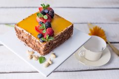 Homemade square cake decorated on top of yellow jelly and berries with mint on light background. Beautiful morning, fresh composition with flowers. Desserts stock photography