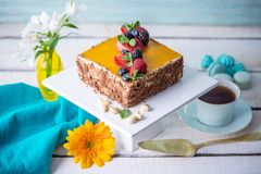 Homemade square cake decorated on top of yellow jelly and berries with mint on light background. Beautiful morning, fresh composition with flowers. Desserts royalty free stock image