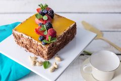 Homemade square cake decorated on top of yellow jelly and berries with mint on light background. Beautiful morning, fresh composition with flowers. Desserts royalty free stock photo