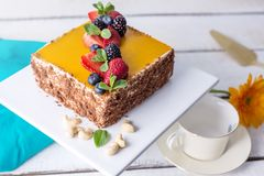 Homemade square cake decorated on top of yellow jelly and berries with mint on light background. Beautiful morning, fresh composition with flowers. Desserts royalty free stock photography