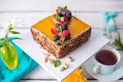 Homemade square cake decorated on top of yellow jelly and berries with mint on light background. Beautiful morning, fresh composition with flowers. Desserts stock images