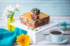 Homemade square cake decorated on top of yellow jelly and berries with mint on light background. Beautiful morning, fresh composition with flowers. Desserts stock photos