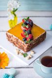 Homemade square cake decorated on top of yellow jelly and berries with mint on light background. Beautiful morning, fresh composition with flowers. Desserts stock photo
