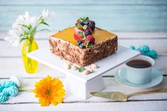 Homemade square cake decorated on top of yellow jelly and berries with mint on light background. Beautiful morning, fresh composition with flowers. Desserts royalty free stock images