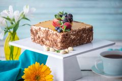 Homemade square cake decorated on top of yellow jelly and berries with mint on light background. Beautiful morning, fresh composition with flowers. Desserts royalty free stock photos