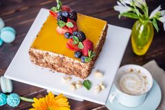 Homemade square cake decorated with yellow jelly on top and berries with mint on dark background. Beautiful morning, fresh composition with flowers. Desserts stock images