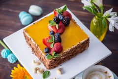 Homemade square cake decorated with yellow jelly on top and berries with mint on dark background stock photos