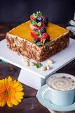 Homemade square cake decorated with yellow jelly on top and berries with mint on dark background. Beautiful morning, fresh composition with flowers. Desserts stock image