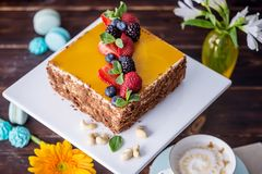 Homemade square cake decorated with yellow jelly on top and berries with mint on dark background. Beautiful morning, fresh composition with flowers. Desserts royalty free stock photo