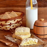 Homemade square cookies on a burlap and basket. Fresh milk in a glass jar with a straw. Small wooden decorative keg and spoon. Royalty Free Stock Photography