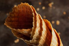Homemade stacked empty cornets or ice cream waffle cones on dark background royalty free stock photography