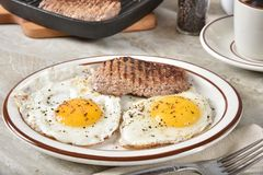 Homemade steak and eggs. Steak and egg breakfast with a cup of coffee royalty free stock photography