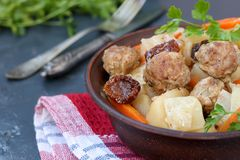 Stewed potatoes with meatballs, carrots and sun-dried tomatoes in a bowl against a dark background stock images