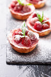 Homemade strawberries tarts with powdered sugar on slate plate, black background. Close up. Homemade strawberries tarts with powdered sugar on slate plate Royalty Free Stock Photos