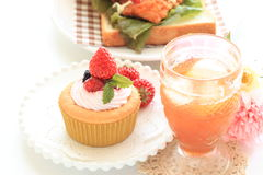 Homemade strawberry cup cake with cream. On pink dish with English tea and flower Stock Photo