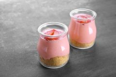 Homemade strawberry dessert with yogurt in glass jars. On grey background Royalty Free Stock Photography