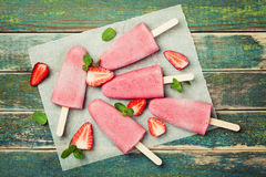 Homemade strawberry ice cream or popsicles on rustic table, frozen fruit juice, top view Royalty Free Stock Image