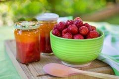 Homemade strawberry jam in different jars and fresh ripe strawbe Stock Photo