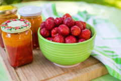 Homemade strawberry jam in different jars and fresh ripe strawbe Royalty Free Stock Photos