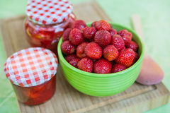 Homemade strawberry jam in different jars and fresh ripe strawbe Royalty Free Stock Photo