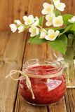 Homemade strawberry jam in glass jar and bunch of jasmine stock photography