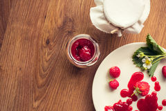 Homemade strawberry jam (marmelade) in jars on wooden background. Royalty Free Stock Images