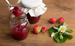 Homemade strawberry jam (marmelade) in jars on wooden background. Stock Photo
