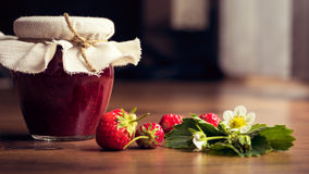 Homemade strawberry jam (marmelade) in jars on wooden background. Stock Photos