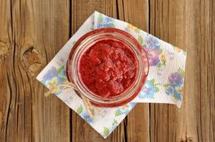 Homemade strawberry jam in open glass jar with hempstring on pap Stock Image