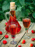Homemade strawberry liquor. On a wooden background royalty free stock photography