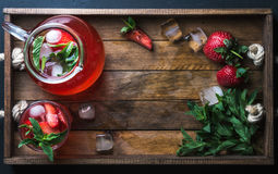 Homemade strawberry mint lemonade served with fresh berries and ice over wooden background, top view, copy space. Homemade strawberry lemonade with mint and ice Stock Image