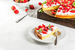 Homemade strawberry pie. Homemade biscuit cake with whipped cream, fresh organic raw strawberries and mint. On a white stone table. Copy space Royalty Free Stock Image