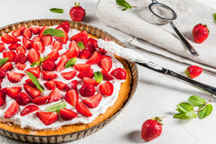 Homemade strawberry pie. Homemade biscuit cake with whipped cream, fresh organic raw strawberries and mint. On a white stone table. Copy space Stock Photos