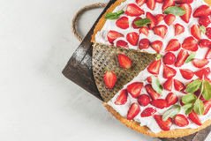 Homemade strawberry pie. Homemade biscuit cake with whipped cream, fresh organic raw strawberries and mint. On a white stone table. Copy space top view Stock Images