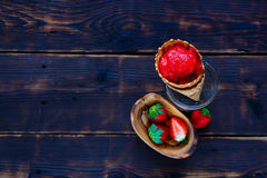 Homemade strawberry sorbet. With fresh berries in waffle cone on vintage wooden background, top view, selective focus. Healthy raw vegan summer dessert concept royalty free stock image
