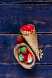 Homemade strawberry sorbet. Waffle cone with homemade strawberry sorbet and fresh berries on vintage wooden background, top view. Healthy raw vegan summer stock photos