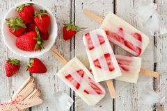 Homemade strawberry vanilla popsicles on rustic white wood. Group of homemade strawberry vanilla popsicles on a rustic white wood background Stock Images