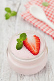 Homemade strawberry yoghurt decorated mint leaves in glass jar on white rustic table, diet and healthy breakfast Stock Photography