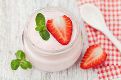 Homemade strawberry yoghurt decorated mint leaves in glass jar on white rustic table, diet and healthy breakfast Stock Photos