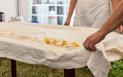 Homemade strudel dough on linen tablecloth ready for making pie according to the traditional recipe. Royalty Free Stock Photography