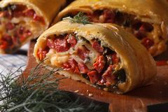 Homemade strudel with ham, cheese and fresh vegetables macro Royalty Free Stock Photos