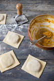 Homemade stuffed with pumpkin ravioli big size on wooden table with bowl Stock Image