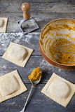 Homemade stuffed with pumpkin ravioli big size on wooden table with bowl Royalty Free Stock Photography