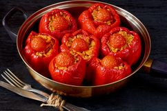 Homemade stuffed red bell peppers with rice and vegetables in a vintage frying pan on the black background. Side view Stock Images